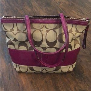 Coach bag with berry purple detailing.